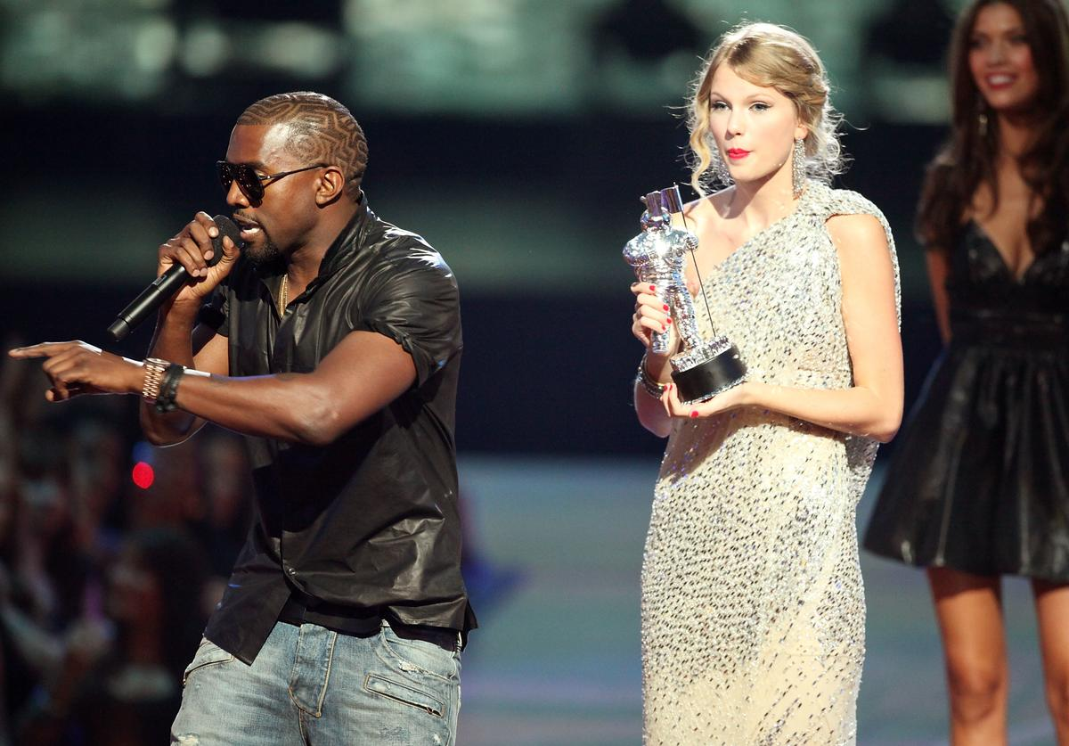 Kanye West (L) jumps onstage after Taylor Swift (C) won the 'Best Female Video' award during the 2009 MTV Video Music Awards at Radio City Music Hall on September 13, 2009 in New York Cit