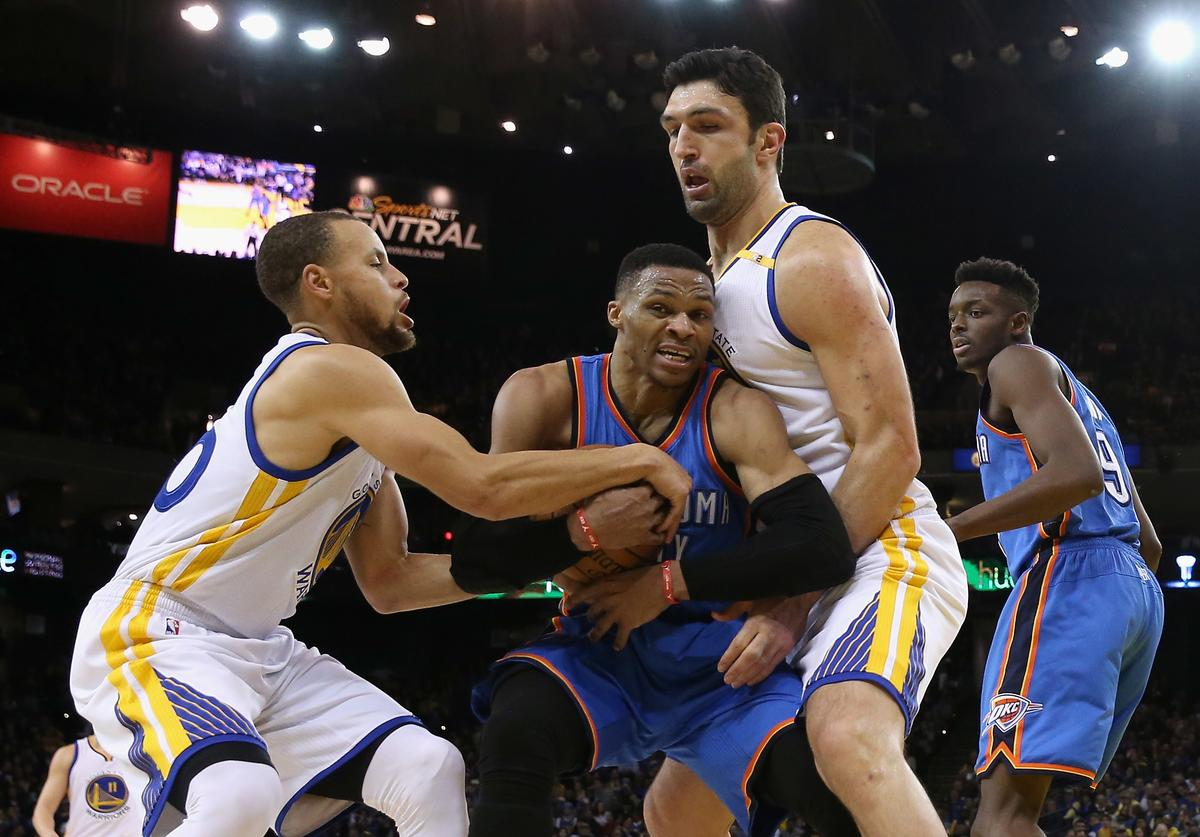 Russell Westbrook #0 of the Oklahoma City Thunder is guarded by Stephen Curry #30 and Zaza Pachulia #27 of the Golden State Warriors at ORACLE Arena on January 18, 2017 in Oakland, California.