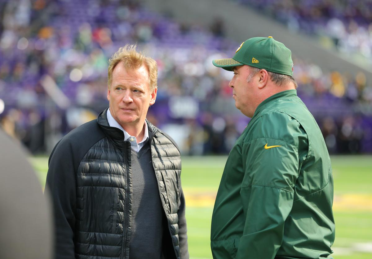 NFL Commissioner Roger Goodell (L) and head coach Mike McCarthy of the Greenbay Packers talk during warmups on October 15, 2017 at US Bank Stadium in Minneapolis, Minnesota
