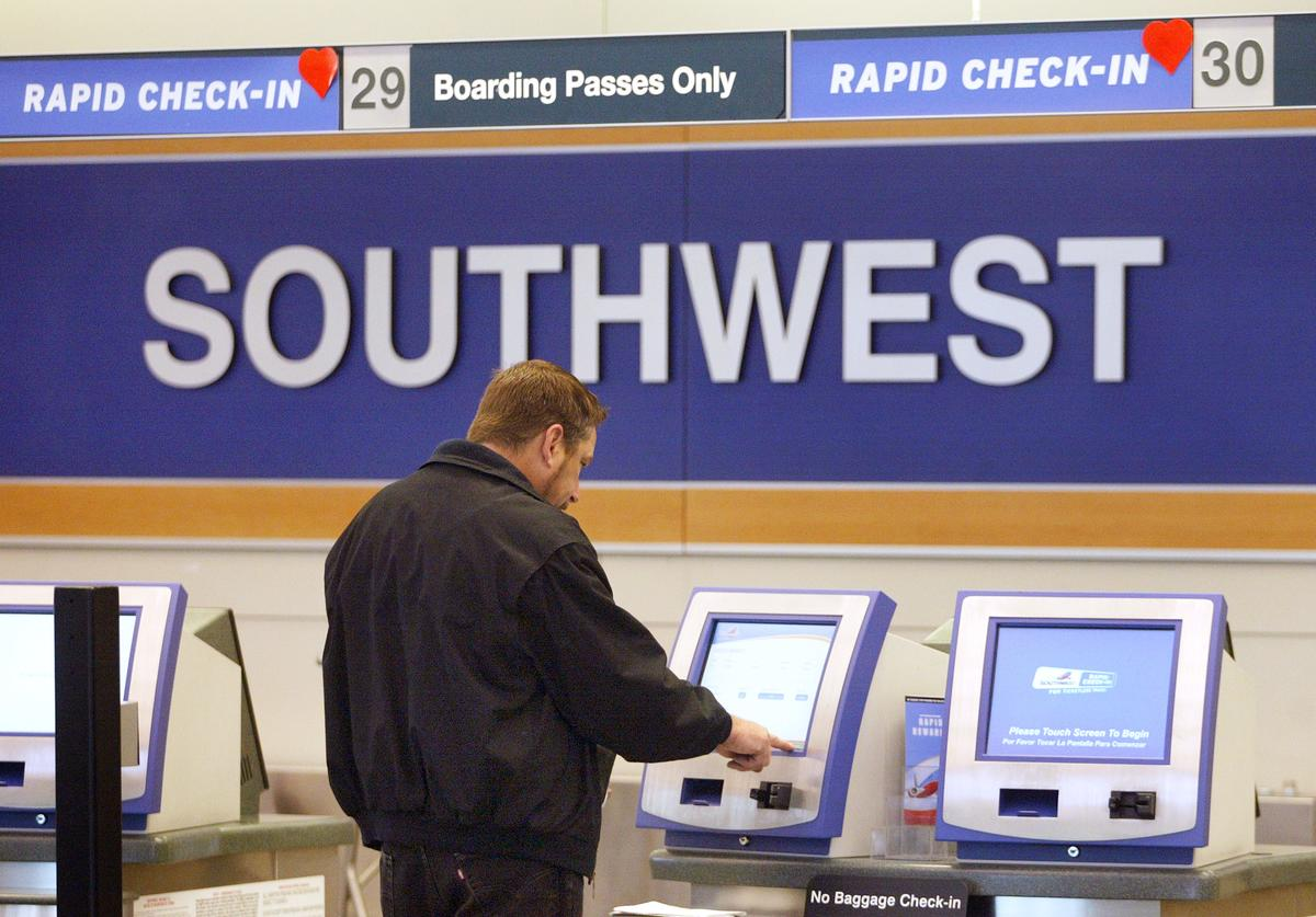 A traveler picks up his boarding pass at a Rapid Check-In kiosk near the Southwest Airlines ticket counter at Midway Airport on March 26, 2004 in Chicago. Southwest Airlines has announced a major expansion to and from Philadelphia International Airport stating that 14 more daily nonstop departures will be added to their schedule effective July 6, 2004. That will bring the number of daily nonstop departures the airline will operate from Philadelphia by mid-summer to 28. US Airways has voiced concern over the expansion