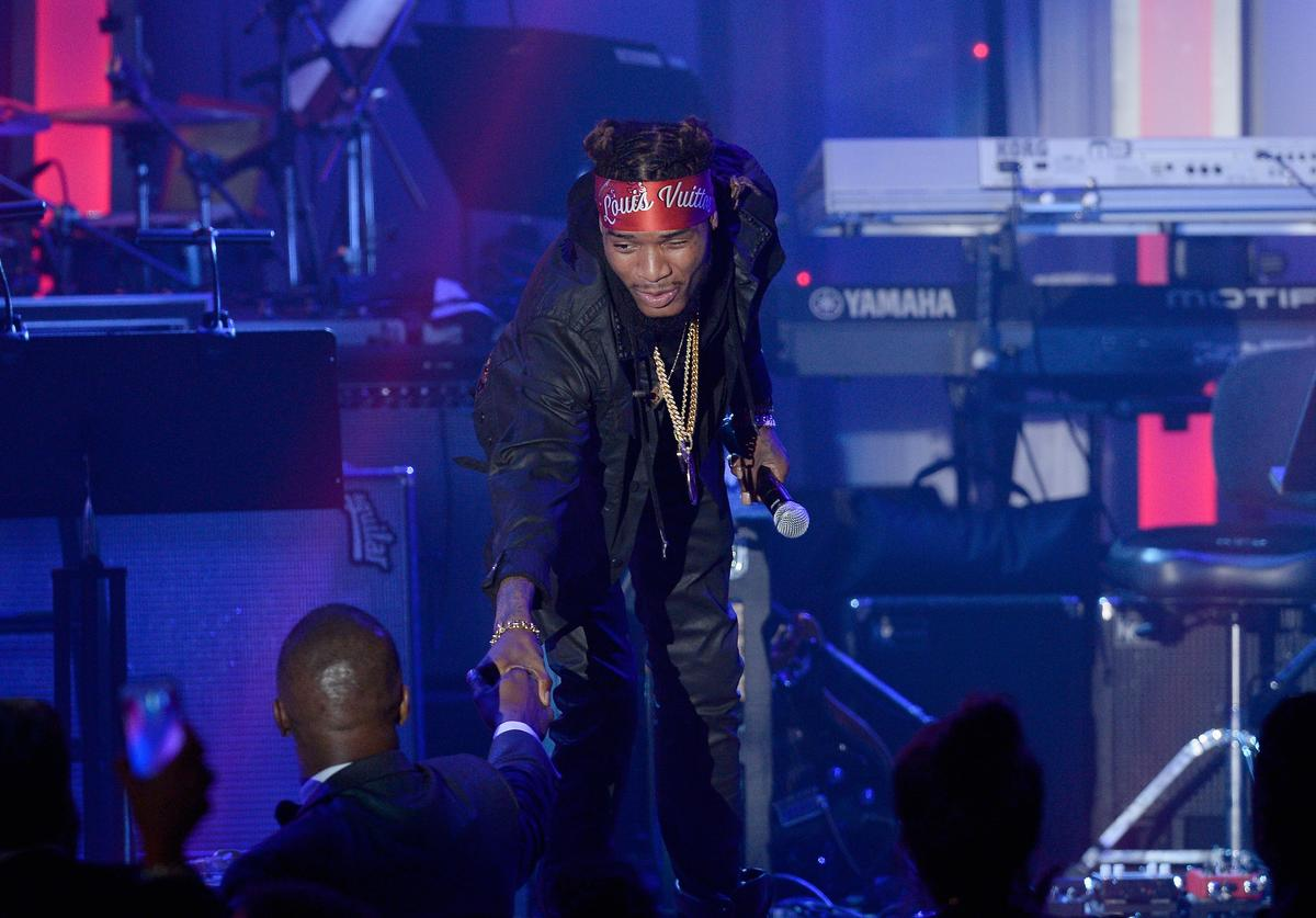 Recording artist Fetty Wap (R, holding microphone onstage) shakes hands with recording artist/actor Jamie Foxx during the 2016 Pre-GRAMMY Gala and Salute to Industry Icons honoring Irving Azoff at The Beverly Hilton Hotel on February 14, 2016 in Beverly Hills, California