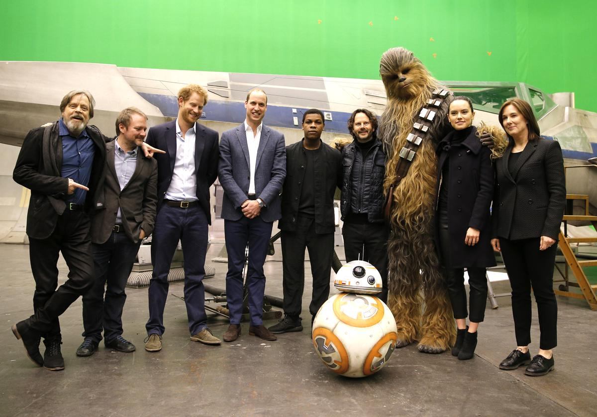 US actor Mark Hamill, US director Rian Johnson, Britain's Prince Harry, Britain's Prince William, Duke of Cambridge and British actor John Boyega, (C) pose with Chewbacca and British actress Daisy Ridley (2nd R) during a tour of the Star Wars sets at Pinewood studios on April 19, 2016 in Iver Heath, England. Prince William and Prince Harry are touring Pinewood studios to visit the production workshops and meet the creative teams working behind the scenes on the Star Wars films