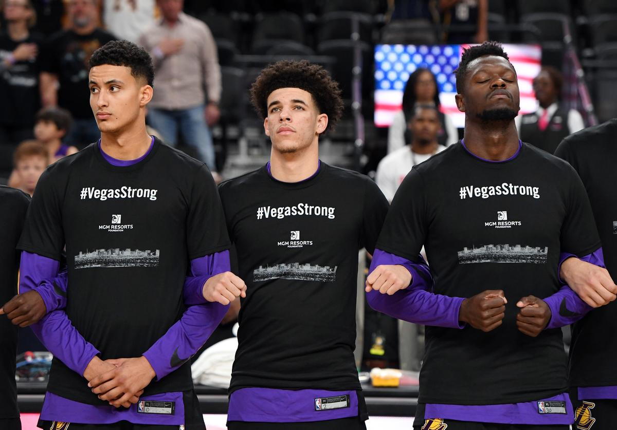 Kyle Kuzma #0, Lonzo Ball #2 and Julius Randle #30 of the Los Angeles Lakers wear #VegasStrong T-shirts as they lock arms during a moment of silence held to honor victims of last Sunday's mass shooting before their preseason game against the Sacramento Kings at T-Mobile Arena on October 8, 2017 in Las Vegas, Nevada. On October 1, Stephen Paddock killed at least 58 people and injured more than 450 after he opened fire on a large crowd at the Route 91 Harvest country music festival. The massacre is one of the deadliest mass shooting events in U.S. history