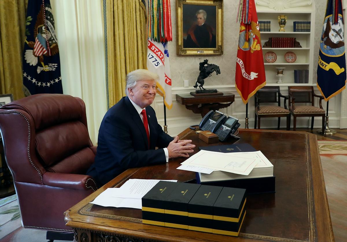 U.S. President Donald Trump talks with journalists before signing tax reform legislation into law in the Oval Office December 22, 2017 in Washington, DC. Trump praised Republican leaders in Congress for all their work on the biggest tax overhaul in decades