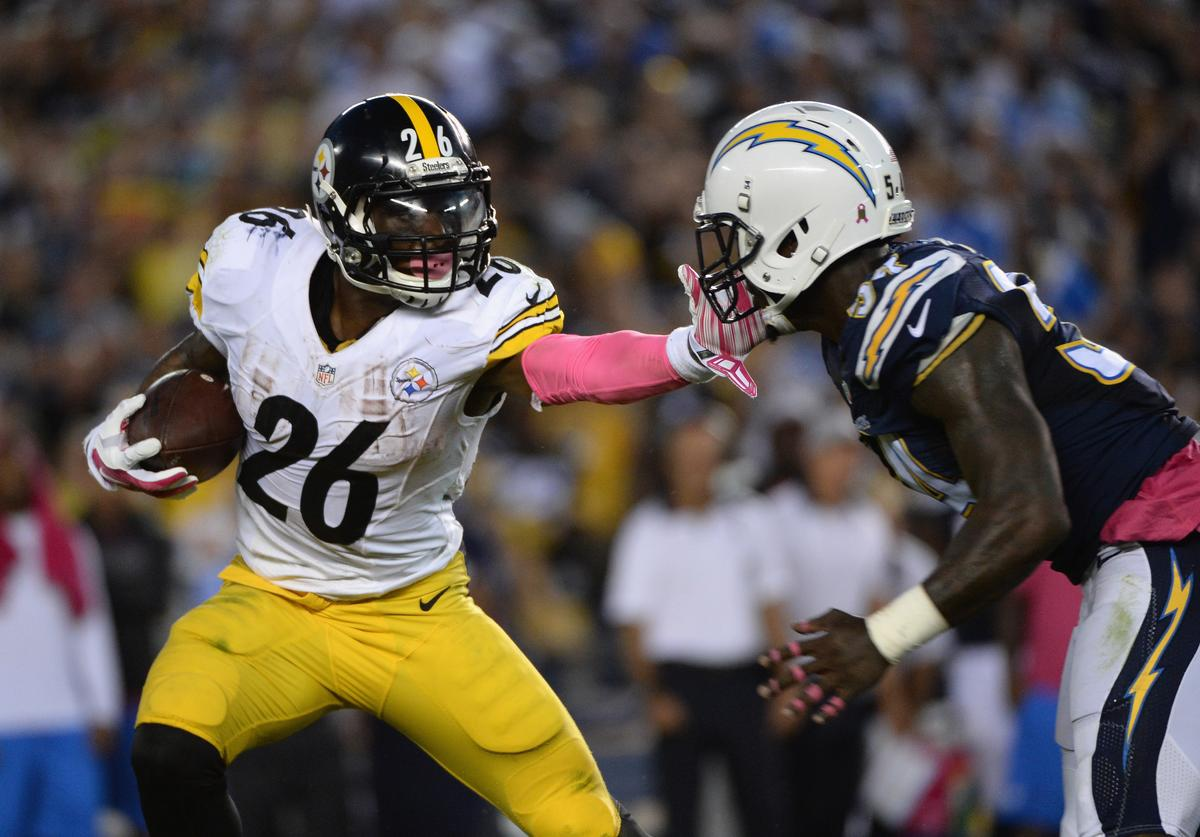 Running back Le'Veon Bell #26 of the Pittsburgh Steelers is pursued by outside linebacker Tourek Williams #58 of the San Diego Chargers at Qualcomm Stadium on October 12, 2015 in San Diego, California