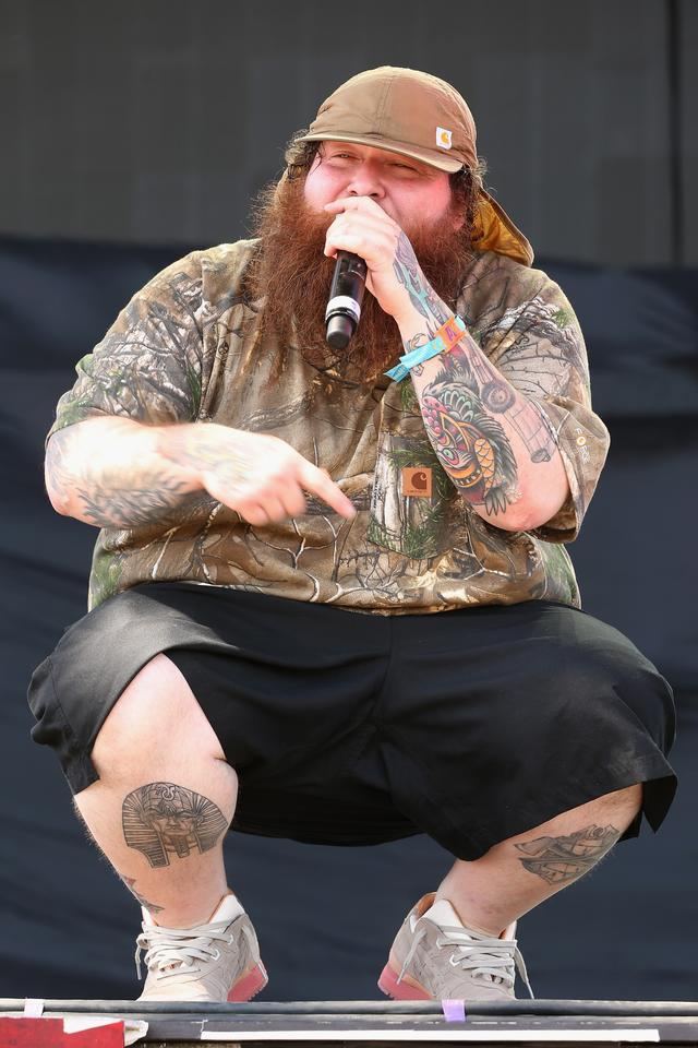 Action Bronson crouching on stage