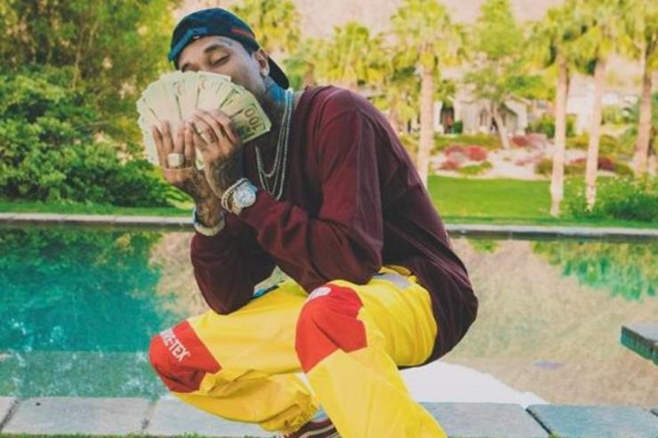 Tyga poses with a stack of money.
